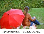 Small photo of Autumn portrait of the woman in leaves with umbrella. Beautiful fashionable girl in the fall under parasol.