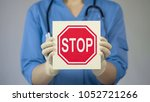 doctor holding stop sign ... | Shutterstock . vector #1052721266