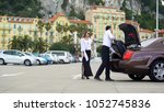 chauffeur putting luggage in... | Shutterstock . vector #1052745836