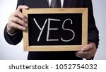 Small photo of Yes written on blackboard, businessman holding sign in hands, business concept