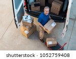 happy delivery man holding... | Shutterstock . vector #1052759408