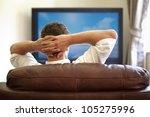 man sitting on a sofa watching... | Shutterstock . vector #105275996