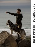 Small photo of Side view of adult man in activewear holding Husky on leash and pointing away exploring coastline.