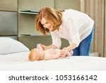 a happy grandmother plays with... | Shutterstock . vector #1053166142