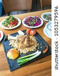 Small photo of Roast or grill lamb shank with roasted potato, onion, rice and salads on wooden table. Concept image for Traditional Turkish cuisine food culture dining table.