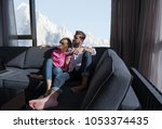 young couple sitting on sofa... | Shutterstock . vector #1053374435