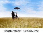 agent in the field with umbrella covering a businessman working outdoor - stock photo