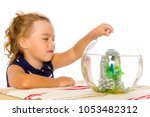 a small tanned girl looks at a... | Shutterstock . vector #1053482312