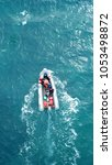 Aerial bird's eye view of inflatable rib boat cruising with small sail boat in turquoise clear water sea