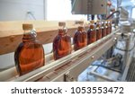bottles of maple syrup line a... | Shutterstock . vector #1053553472