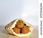 Small photo of Falafel balls in a pita bread on wooden table over white background.