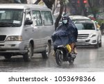 people with a raincoat ride on...   Shutterstock . vector #1053698366