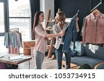 Stock photo what do you think about this one beautiful young woman helping to choose clothes to her customer 1053734915