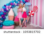 two young women in pink dresses ... | Shutterstock . vector #1053815702