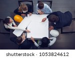 top view of people around table ... | Shutterstock . vector #1053824612