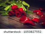 Stock photo red rose bouquet and rose petals on the wooden floor vintage effect 1053827552