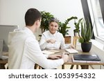 Small photo of Candid shot attractive confident middle aged female employer sitting at desk with copybook, making notes during job interview with prospective unrecognizable young male candidate. Film effect
