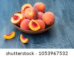 ripe peaches in a wooden bowl.... | Shutterstock . vector #1053967532