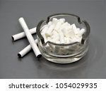 cigarette filters in ashtray | Shutterstock . vector #1054029935