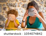 Small photo of Mom and daughter at the breakfast table holding their bowl with both hands and drinking. Familiar morning