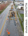 Small photo of High angle view of pipes and equipment that will replace old, antiquated water lines on a city street.