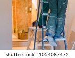 legs of worker with green... | Shutterstock . vector #1054087472