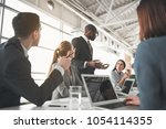 low angle of managers sitting... | Shutterstock . vector #1054114355
