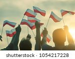Stock photo poland patriots back view people raising polish flags up to the sky 1054217228
