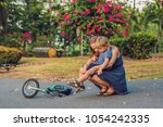 the boy fell off the bicycle ... | Shutterstock . vector #1054242335