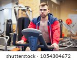 fitness man on bicycle doing... | Shutterstock . vector #1054304672