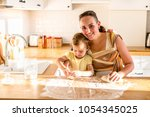 mother with daughter in sling... | Shutterstock . vector #1054345025