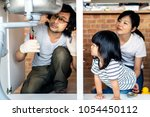 asian family fixing kitchen sink | Shutterstock . vector #1054450112