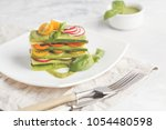 Stock photo raw zucchini lasagna with vegetables and pesto sauce light background vegetarian raw diet concept 1054480598