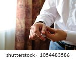 the man puts on his wristwatch. ... | Shutterstock . vector #1054483586
