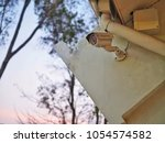 Small photo of Closed circuit television cameras installed on the wall under the roof for watch the events that occur or observe the dangers outside, Security camera, White CCTV and sky at sunset in the evening