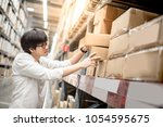 young asian man picking paper... | Shutterstock . vector #1054595675