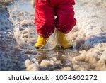kid in yellow rainboots jumping ... | Shutterstock . vector #1054602272