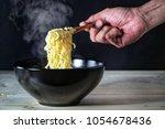 hand holding wooden chopsticks... | Shutterstock . vector #1054678436
