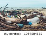 spilled garbage on the beach of ... | Shutterstock . vector #1054684892