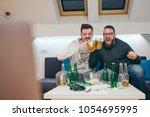 friends watching sport on tv at ... | Shutterstock . vector #1054695995