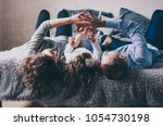 young family are lying on bed... | Shutterstock . vector #1054730198