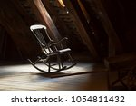 old rocking chair on a dim attic | Shutterstock . vector #1054811432