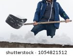 young man clean a roof from... | Shutterstock . vector #1054821512