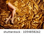 woman leg on gold silk fabric... | Shutterstock . vector #1054858262