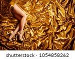 woman leg on gold silk fabric... | Shutterstock . vector #1054858262