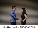 Small photo of Two Chinese business people (a man in a suit and professionally dressed woman) shake hands in agreement and accord over a deal in the daytime against a plain background.