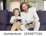 happy dad laughing playing... | Shutterstock . vector #1054877102