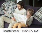 cute kid son holding newspaper... | Shutterstock . vector #1054877165