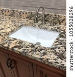 Small photo of bathroom granite counter over wooden vanity cabinet and white rectangular sink with chrome faucet