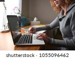 a young woman using a laptop in ... | Shutterstock . vector #1055096462